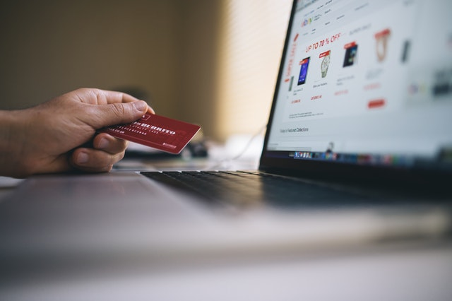 A close up of a person's hand holding a credit card in front of a laptop with an online shopping website pulled up on the screen.