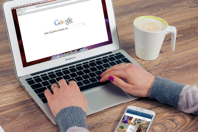 A photo of a person's hands typing into a Google search bar on a MacBook air. A cup of coffee and a smart phone are also on the wooden table.